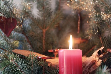 Red candle of an Advent wreath with fir branches. Stock Photo