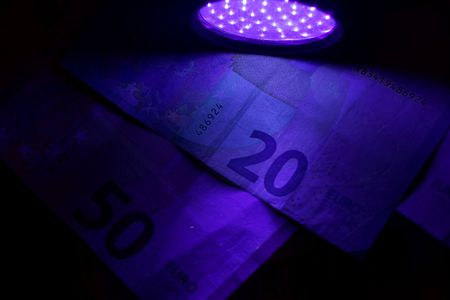 Banknotes in the beam of an UV flash light.