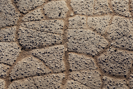 Broken and fragmented pavement of a road.