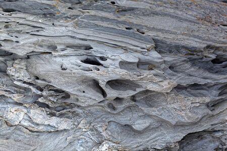 La surface d'une roche métamorphique grise altérée.