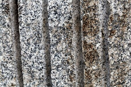 Drilled holes in a granite rock surface from stone mining. Imagens
