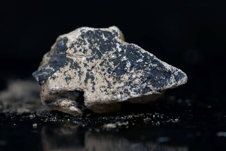 A macro photo of calcium carbide or calcium acetylide with a black background.