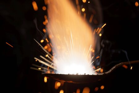 Macro photo of bursting gunpowder with a black background.