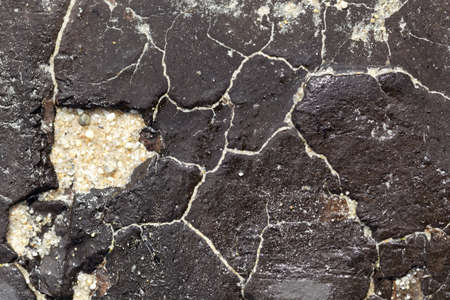 Texture of a tar mat on a beach from an oil spill in Brittany, France. Archivio Fotografico