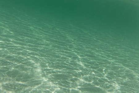 Underwater photo of light textures on a sandy beach. Stock fotó