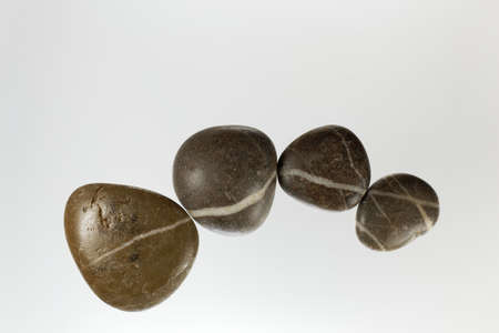 A row of dark pebbles with white veins and a light background