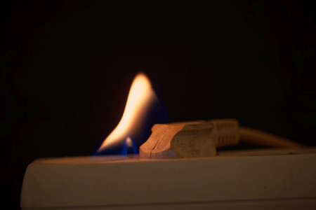 Burning plug socket with a flame and a dark background. Standard-Bild
