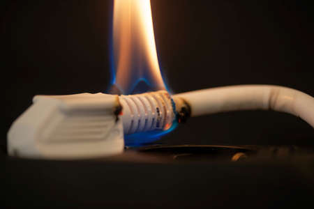 Burning plug socket with a flame and a dark background. Standard-Bild - 163326956