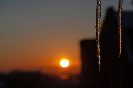 Sunset winter scene with two icicles in a city. 스톡 콘텐츠