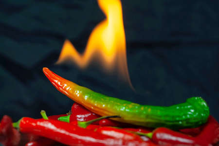 Green and red chillies with flames and a dark background Banco de Imagens