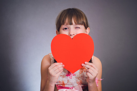 protruding eyes: The girl hides behind heart and winks
