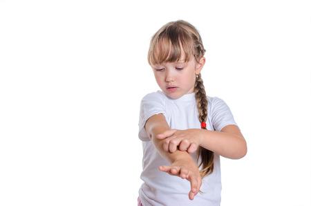 La bambina in una canottiera bianca gratta una mano