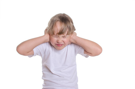 The little girl in a white undershirt closed hands ears from noise. Stock Photo