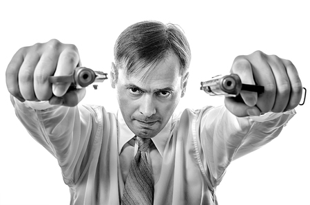 gun sight: A man in a white shirt with two pistols aiming to shoot Stock Photo