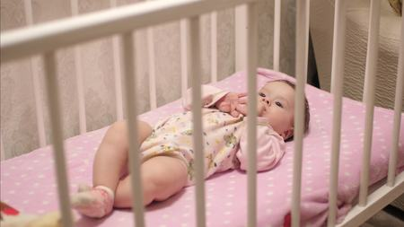 goffo: Baby lies on back in crib. Slow motion,