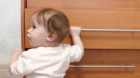 Small child, learns to walk, holding handle of closet, in children room.