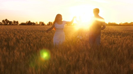 Mom and Dad carry small daughter in arms across field of wheat in beautiful rays of sunset. Baby with parents playing and smiling in a field with wheat. Stok Fotoğraf