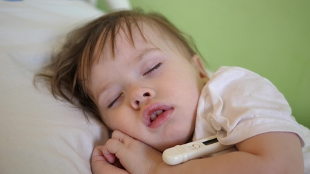Child temperature is measured with thermometer in hospital ward. close-up. Baby sleeps in hospital ward on a white bed.