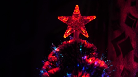Christmas star glows with red lights on Christmas tree in childrens room, Christmas tree is decorated with a garland and flashes in blue and red