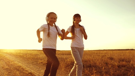 young girls are training at sunset and listening to music. teen girls in headphones doing sports jogging in the countryside.