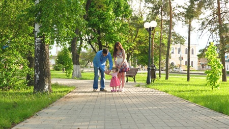 Little baby learning how to walk with mom and dad, happy family walking in summer Park