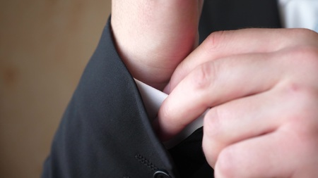 man in blue tie and black suit straightens sleeve of a white shirt.