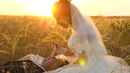 bride caresses groom with grass stalk in face. happy family is lying in field in rays of beautiful sunset. young woman kisses her beloved man on lips on summer evening in the grass. happy family concept Banco de Imagens