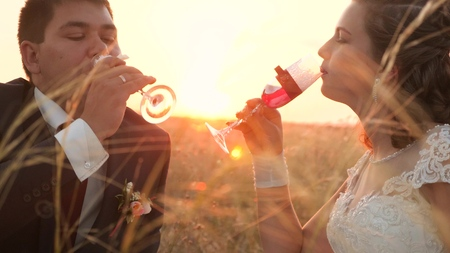 Happy bride and groom drink champagne from beautiful glasses in bright rays of sun. enamored newlyweds drink wine in meadow in rays of a beautiful sunset. happy wedding concept. close-up. Standard-Bild