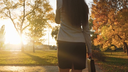 business woman talking on cell phone. woman walks in park in rays of sunset with black briefcase for documents. beautiful female legs in skirt and pantyhose are walking along the sidewalk.