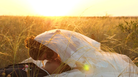 bride caresses groom with grass stalk in face. happy family is lying in field in rays of beautiful sunset. young woman kisses her beloved man on lips on summer evening in the grass. happy family concept Stock Photo
