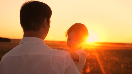 Happy dad and little daughter sitting in her arms at sunset bright sun. Girl laughs playing with dad on evening walk. Close-up