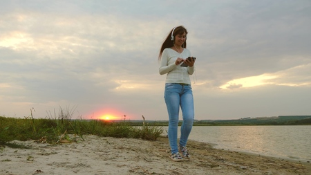 girl with headphones walking along beach with tablet and listening to music. girl in rays of sunset walking on beach and checking mail on a tablet online 免版税图像