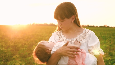 Little baby is yawning in arms of young girl in glare of sunset. Young nanny walks with small kid Stok Fotoğraf