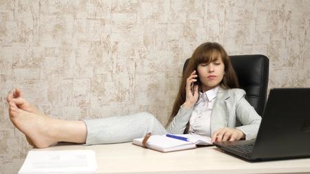 mooie zakenvrouw zittend in een stoel met voeten op tafel. meisje aan het werk op kantoor aan de telefoon aan de tafel en rusten.