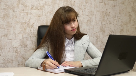 girl sitting in chair in office at computer and takes notes in notebook. young female entrepreneur working behind the laptop. secretary writes pen in a notebook 스톡 콘텐츠