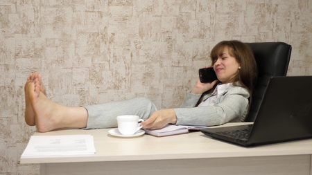 beautiful business woman sitting in an armchair with feet on table resting and drinking tea, coffee. girl at work in office negotiates on mobile phone and works on a computer.