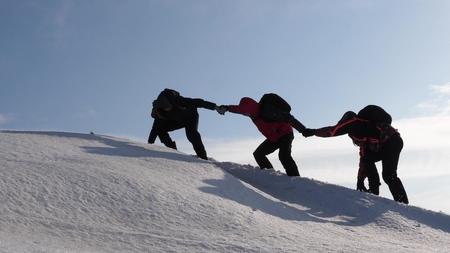 klimmers hand in hand klimmen naar de top van een besneeuwde berg. het team van reizigers in de winter gaat naar hun doel om moeilijkheden te overwinnen. goed gecoördineerd teamwork toerisme.