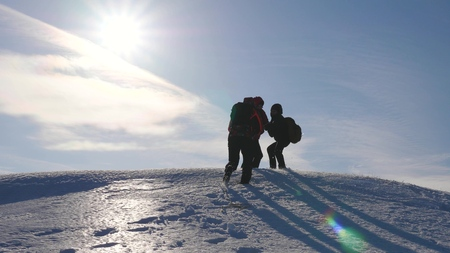 three Alpenists climb rope on snowy mountain. Tourists work together as team shaking heights overcoming difficulties. silhouettes of travelers rise to their victory up hill on ice in rays of the sun.