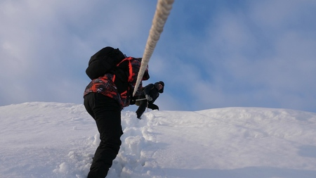 Travelers descend by rope from snowy hill. Alpinists team in winter down rope from the mountain. well-coordinated teamwork tourism in winter