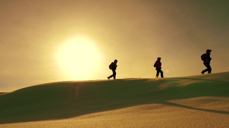 team of travelers follow each other along snow ridge against backdrop of yellow sunset. coordinated teamwork of tourists in the winter. teamwork of people in difficult conditions.
