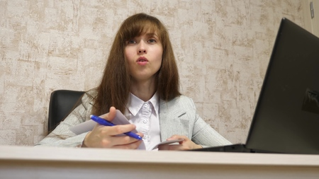 beautiful girl sitting in a chair in office and talking and making notes in bloknot. young female entrepreneur working with a client in an office