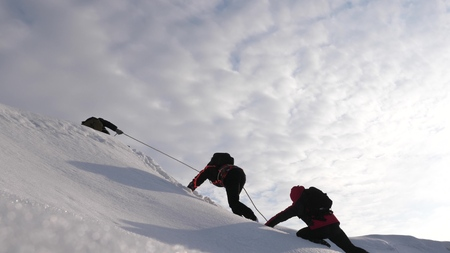 Travelers climb rope to their victory through snow uphill in a strong wind. tourists in winter work together as team overcoming difficulties. three Alpenists in winter climb rope on mountain.