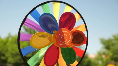 toy pinwheel multi-colored, rotated by the wind against a blue sky. colored decorations for a childrens party. concept of a beautiful holiday. Foto de archivo