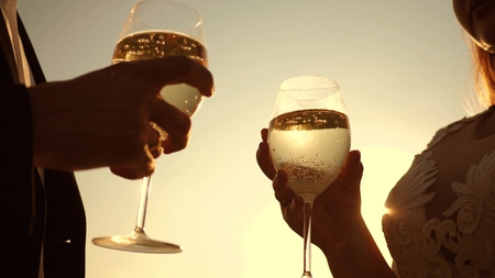 couple in love holding wine glasses with sparkling wine on background of sunset. closeup. teamwork of loving couple. celebrating success and victory. champagne sparkles and foams in sun. Slow motion