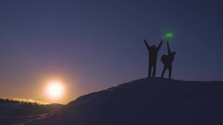 Man teamwork business travel silhouette concept. two hikers winter snow tourists climbers climb to the top of mountain lifestyle . overcoming hardships the path to victory, teamwork, important points 版權商用圖片