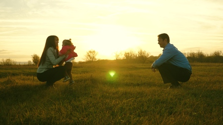 mom and dad play with kid on the grass at sunset. family happiness concept. baby goes on lawn from dad to mom. child takes first steps in park.