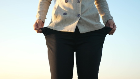 Girl is bankrupt. Beggar business. Ruined enterprise. Woman debtor turns out empty pockets against blue sky Stock Photo