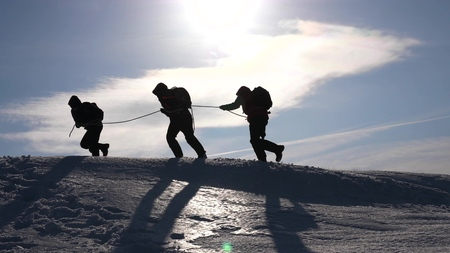 teamwork desire to win. Climbers on a rope help a friend climb to the top of the hill. Silhouette of travelers in winter on a hill in the bright rays of the sun. concept of sports tourism.