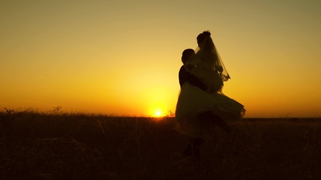Young bride and groom circling on background of romantic red sunset. Honeymoon. The relationship between man and woman Фото со стока