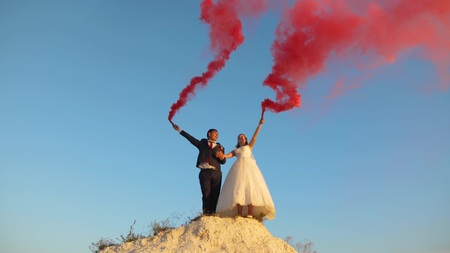 Happy bride and groom waving colored pink smoke against blue sky and laughing. Honeymoon. Romance. Relationship between man and woman